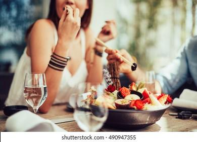 jovem sentada no pátio de restaurantes e comer frutas suculentas
