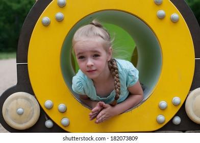 Young girl sitting in crawl tube