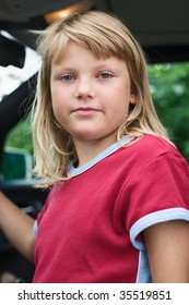 Young girl sitting in driver's seat of car