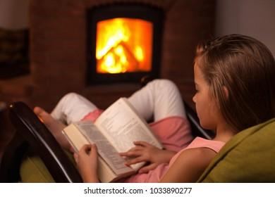 Young girl sitting in front of fireplace reading a book in the evening - relaxation concept
