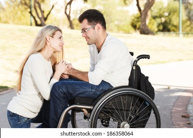 Young girl sitting in front of her boyfriend in a wheelchair in the park
