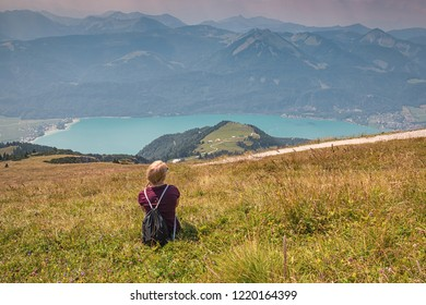 Young girl sitting in the grass and looking on the Alps.