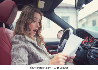 Young girl sitting inside of a car and reading fine papers, looking frustrated.