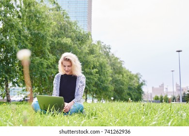 young girl sitting with laptop in the city Park on the grass