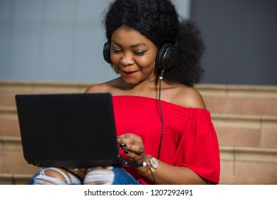 young girl sitting with laptop listening to music using headphones while smiling.