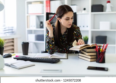 A young girl sitting in the office at the computer Desk and working with a book.