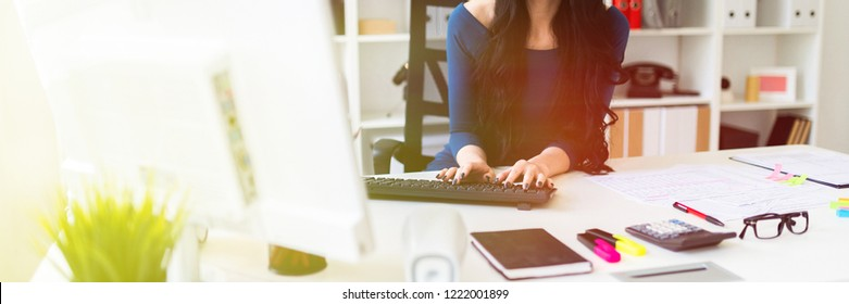 A young girl is sitting at the office at the table and typing text on the keyboard.