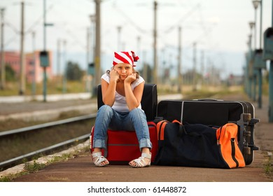 Young girl sitting on bag and waiting for train in the station