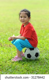A young girl sitting on a ball