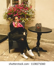 A young girl is sitting on a chair, a small courtyard, talking on the phone, mobile communication, emotions, love, contact, conversations, talking on the phone, a beautiful girl communicates.