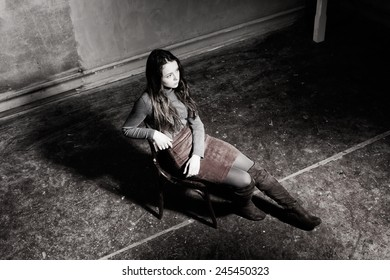 young girl sitting on a chair in the gloomy place