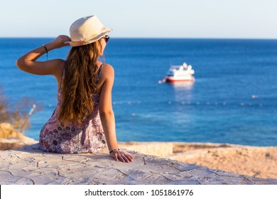 Young girl sitting on the coast looking to the boat at azure sea, Sharm El sheikh, Egypt