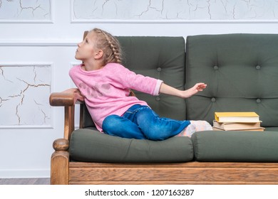 young girl sitting on the couch turned away from a pile of books, showing a reluctance to learn
