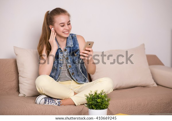 young girl sitting on the couch talking on the phone and listening to music on headphones