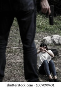 Young girl sitting on a dirt ground is threatened by a mysterious gunman.