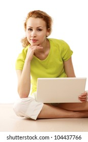 A young girl sitting on the floor with a laptop isolated on white background