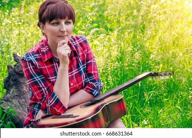 Young girl sitting on the grass in the field and plays the guitar. Beautiful nature at bright sunny summer day. Camping.