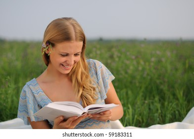 Young girl sitting on green grass and reading a book