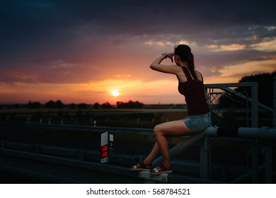 Young girl sitting on the guardrail highway and looking toward the horizon with the setting sun. Pose with arms screening refers to the emotional subtext. Background is out of focus.