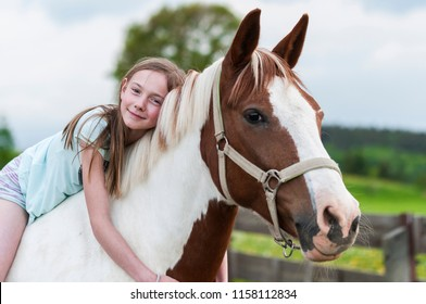 Young girl is sitting on a horse, hugging it and smiling at the camera./Young girl is sitting on a horse