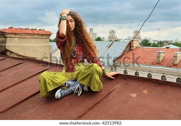Young girl sitting on a iron roof