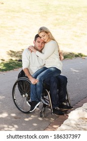 Young girl sitting on the lap of her boyfriend in a wheelchair in the park