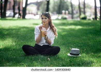 Young girl is sitting on the lawn. Drink juice and rest. They had a picnic. Cheerful mood and smile.