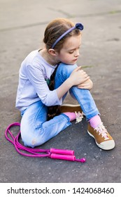 Young girl sitting on the pavement with skipping rope