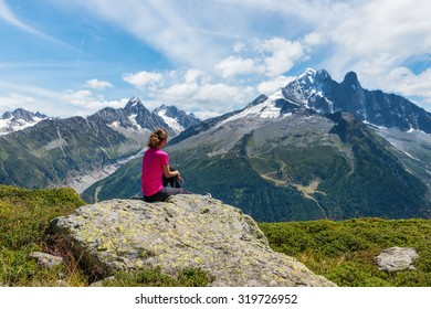 Young girl sitting on a rock and looking at beautiful mountains in the sunny summer day.