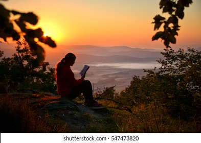 Young girl sitting on the rock over valley and reading a book during calm summer sunset full of warm light