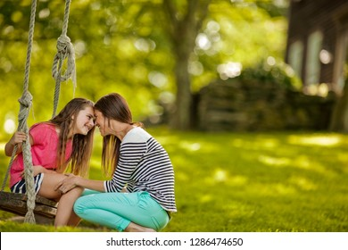 Young girl sitting on a rope swing affectionate nudges her mother.