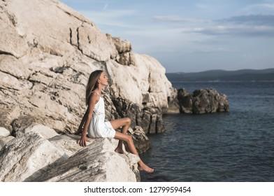 young girl sitting on sea