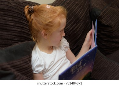 Young girl sitting on the sofa reading a book