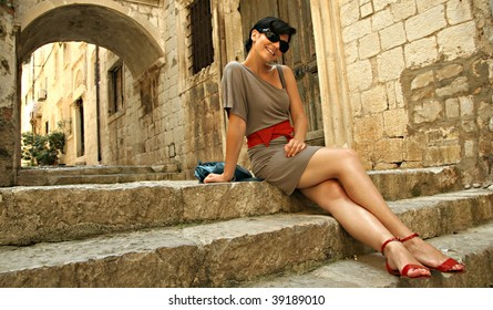 Young girl sitting on stairs in a old town