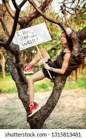 "Young girl sitting on a tree in the park with a poster ""I live like I want!""  International Womens Day concept."