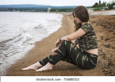 Young, girl sitting on white sandy beach looking into the distance