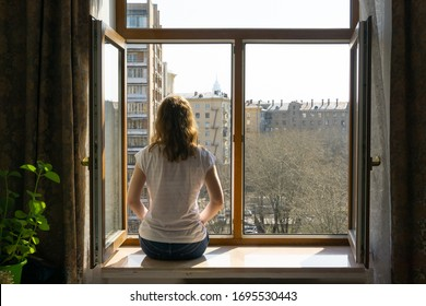A young girl sitting on a window sill at home during coronavirus epidemic