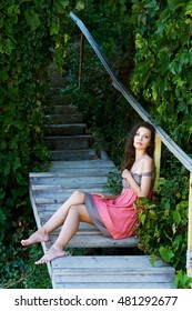 Young girl sitting on wooden stairs