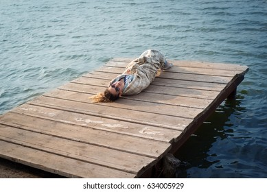 young girl is sitting on a wooden bridge