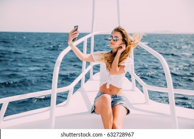 Young girl sitting on the yacht and taking selfie with sea