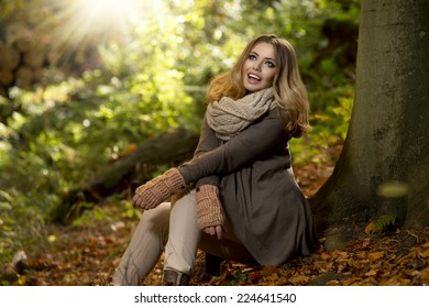 Young girl sitting outdoor in autumn scenery. Beauty smile
