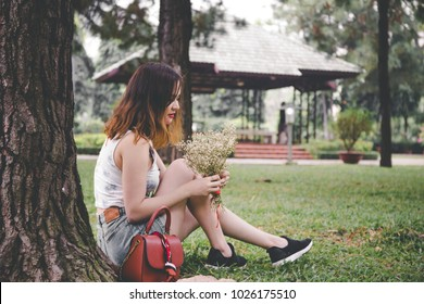 The young girl sitting in park garden.
