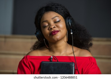 young girl sitting in red camisole with laptop listening to music using headphones with eyes closed while smiling.