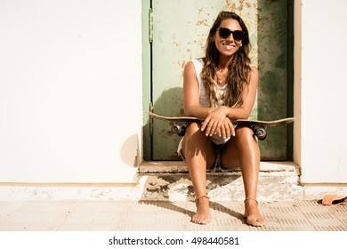 young girl sitting with a skateboard in front of grunge door.