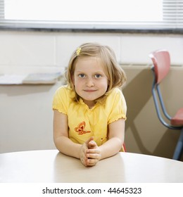 Young girl sitting at table in school classroom. Square format.
