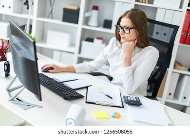 Young girl sitting at the table and working with a computer, documents and calculator