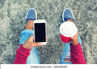 Young girl sitting and using smart phone.