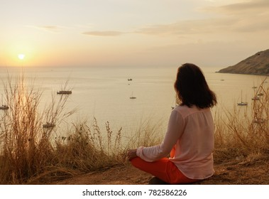 Young girl sitting in yoga lotus meditation position in front to seaside on the rocks an watching the sun goes down in a golden hour. sunset over sea.