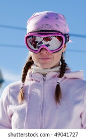 Young girl in ski mask on winter sport resort in european mountains
