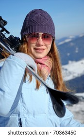 Young girl with ski over winter background